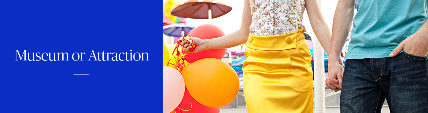 Woman holding red and yellow balloons and holding hands with a man at a carnival