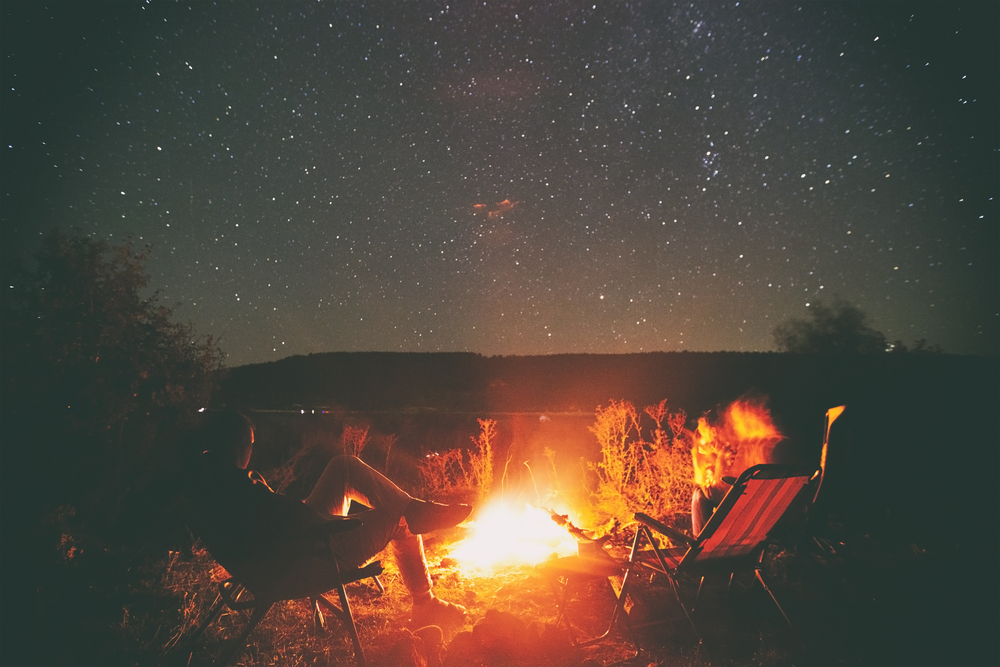 Two people sitting in camp chairs around a campfire under a starry sky