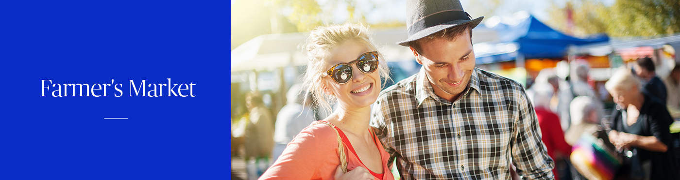 Woman in sunglasses and man in hat on a casual date at a farmer's market