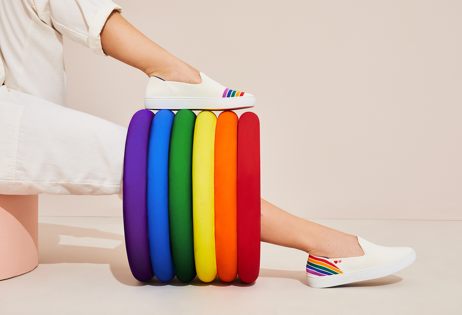The Sneaker in Rainbow shown from the side on-model with a prop.