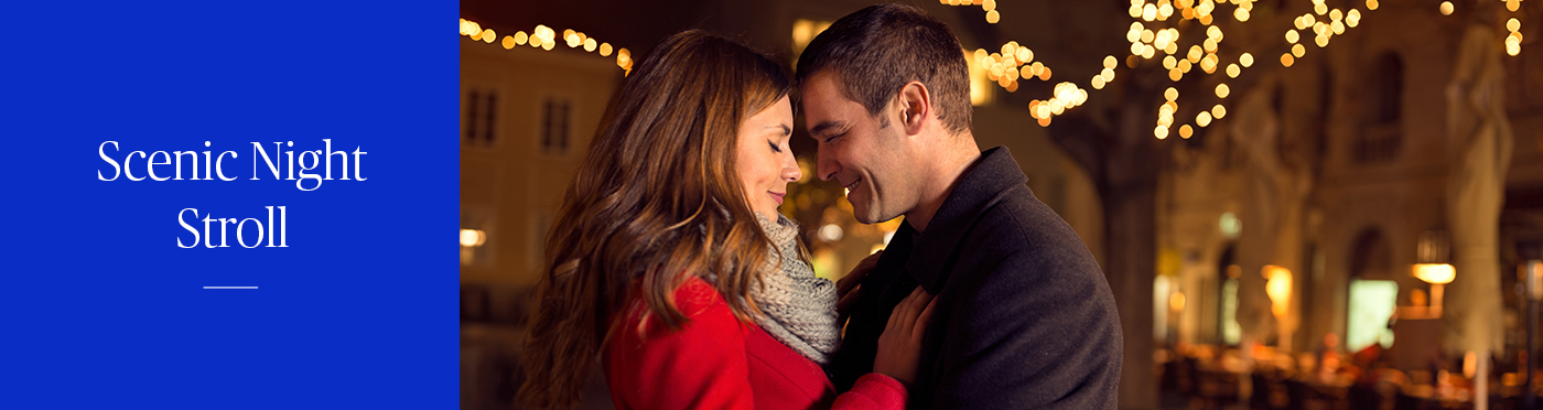 Man and woman in romantic embrace on softly lit scenic street